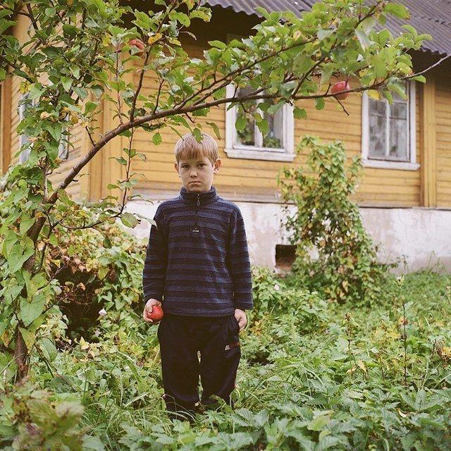 Девятилетний Саша позирует перед своим домом