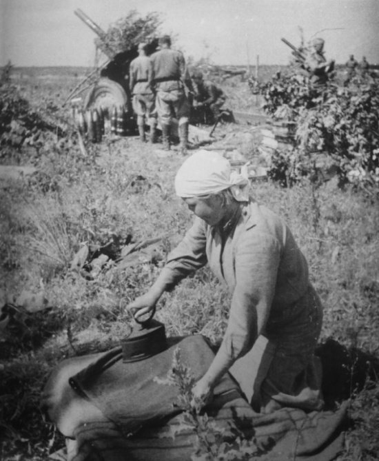 Великая отечественная войны. Женщина-боец гладит юбку рядом с гаубицами.