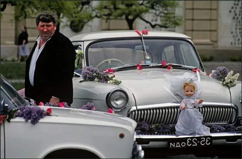 Водитель со своей машиной, украшенной свадебными цветами и куклой, ждет жениха и невесты после их свадьбы. Одесса, Украина, 1982. Автор фото: Иэн Берри