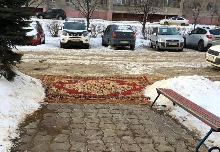 Вместо плитки коммунальщики прикрыли дыру у подъезда ковром