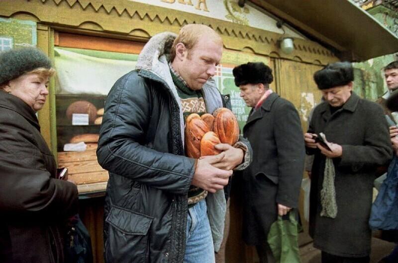 Мужчина уходит от хлебного киоска с несколькими буханками хлеба. Доллар США в настоящее время стоит 398 рублей, а средняя месячная зарплата в России составляет примерно 5000 рублей (12 долларов США) в месяц, 3 ноября 1992 года