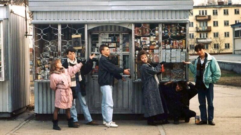 Молодые люди возле ларька с широким ассортиментом товаров, Россия, 1990 е годы